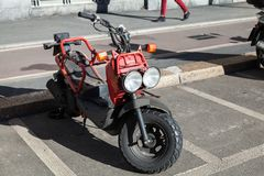 Red Honda Zoomer scooter, close up. Milano, Italy - January 19, 2018: Red  Zoomer 49cc scooter developed by Honda stands on a parking lot in the city Royalty Free Stock Photo