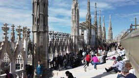 Milano, Italy. People walking and sitting on the roof of the Duomo. Terrace overlooking the city. Spring time stock video footage