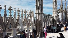 Milano, Italy. People walking and sitting on the roof of the Duomo. Terrace overlooking the city. Spring time stock footage