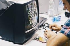 Milano l'ITALIA OTTOBRE 2018 - la gente che gioca con il video gioco d'annata alla settimana dei giochi a Milano (fiera del Rho) fotografia stock