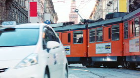 Milano Orange Tram passing by. Crossing a white and a black taxi stock video footage