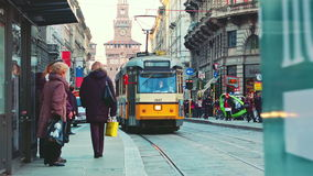 Milano Orange Tram passing by. And people stepping out at the Tram Stop stock footage