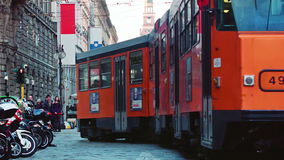 Milano Orange Tram passing by. Milano Orange Trams passing by with a young guy running to catch it stock video footage