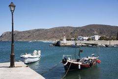 The Cretan resort of Milatos on the north coast. Milatos, Crete, Greece. 2017. The small fishing harbour with mountains joining the Sea of Crete Stock Image