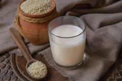 Milch des indischen Sesams im Glas- und Sesamsamen im Tongefäß auf einer Tabelle Lizenzfreie Stockfotografie
