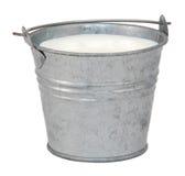 Milch in einem Miniaturblecheimer Stockbild