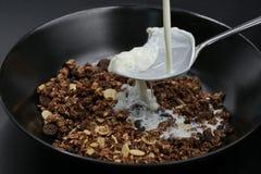 Milch fließt auf Löffel in Schokolade muesli, Getreide stockfotografie