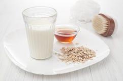 Milch, Honig, Hafermehl in den selbst gemachten Kosmetik der Rezepte auf weißem Hintergrund Stockfotos