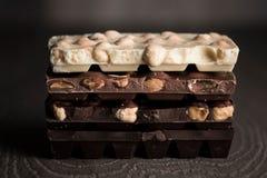 Milch und dunkle Schokolade auf einem Holztisch Lizenzfreies Stockbild