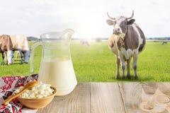 Milch und Hüttenkäse auf einem Hintergrund von Wiesen mit Kühen Lizenzfreies Stockbild