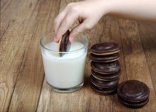 Milch und Plätzchen Kind-` s Hand mit Plätzchen stockfotografie