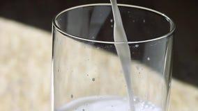 Milch wird in ein Glas auf einem Holztisch gegossen stock footage