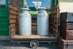 Milchkannen auf hölzerner Laufkatze Lizenzfreies Stockfoto