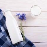 Milchschale und -flasche auf Holztisch Stockfoto