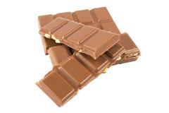 Milchschokoladestangen mit den Haselnüssen lokalisiert auf einem weißen Hintergrund Stockfotografie
