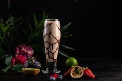 Milchshake mit Banane und Schokolade in einem hohen Glas auf einem dunklen Hintergrund stockbild