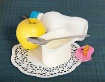 Milchspeise, Apfel, soother und Serviette Stockfotografie