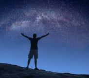 Milchstraße des Mannes in einem sternenklaren Himmel Stockfotografie