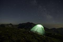 Milchstraße-Galaxie Kemping Purpurrote Sterne des nächtlichen Himmels über Bergen Stockfoto