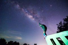Milchstraße und Million Stern im Himmel über der thailändischen Drachestatue Lizenzfreie Stockfotos