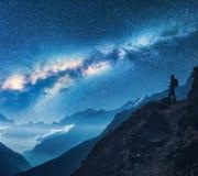 Milchstraße und Schattenbild der stehenden Frau auf dem Berg Stockfotografie