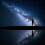 Milchstraße und Schattenbild einer stehenden Frau auf Berg Lizenzfreie Stockfotografie