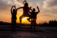 Mild silhouettes of boys and girls at sunset playing hopscotch Royalty Free Stock Image
