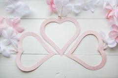 Mildern Sie das rosa Herz, das vom Papier mit den weißen und rosa Blumen auf weißem Holztisch gemacht wird Lizenzfreies Stockfoto