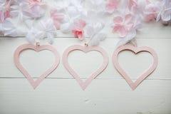 Mildern Sie das rosa Herz, das vom Papier mit den weißen und rosa Blumen auf weißem Holztisch gemacht wird Stockfotos