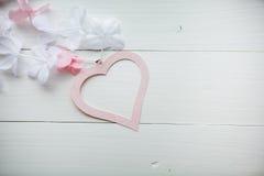 Mildern Sie das rosa Herz, das vom Papier mit den weißen und rosa Blumen auf weißem Holztisch gemacht wird Lizenzfreie Stockfotos