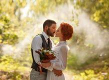 Mildern Sie Kuss der Braut und des Bräutigams unter Offenem Himmel Stockfotos
