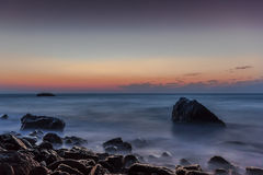Mildern Sie Wellen auf dem Felsen Stockbilder