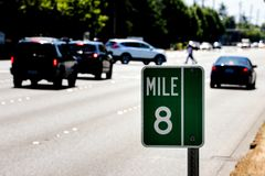 Mile Marker 8 sign on a post with traffic and a road. Showing trees stock photo