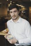 Milenar seguro novo comendo um café Fotos de Stock