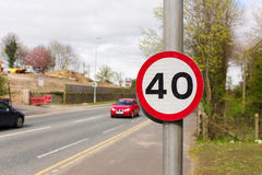 40 Miles per Hour Speed Zone. Urban 40 miles per hour speed limit sign used in the United Kingdom with defocussed traffic in the background Royalty Free Stock Images