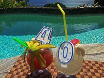 Happy Birthday 40th Ideas Tropical Cocktail. Drinks by the pool 40 birthday candles sit in frosty drinks by the water overlooking the ocean in paradise Bananas royalty free stock images