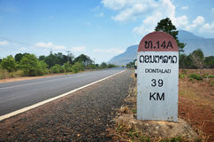 Milestone go to DONTALAD at Pakse in Champasak, Laos. A milestone is one of a series of numbered markers placed along a road or boundary at intervals of one mile Stock Photography