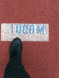 Milestone (in metric). Leg with black shoes (with shoelaces) and pants, stepping on a 1000 meter mark of a jogging track royalty free stock photography