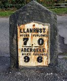 Milestone, North Wales, ancient, iron on stone, figures in miles and furlongs. An ancient North Wales milestone giving the distance in miles and furlongs from stock images