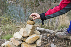 Milestone. A person putting an stone in the top of a milestone for hiking Stock Photography
