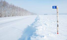 Milestone pillar next to empty icy highway Stock Image
