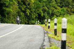 Milestone on the road. Milestone beside the road and rider driving a motorcycle with forest background Stock Photos