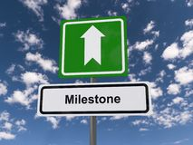 Milestone. Text 'Milestone' in black letters on white highway style sign with a green sign above containing a large white arrow, background of blue sky and cloud Stock Photo