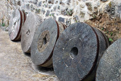 Milestones. Antique millstones standing near the wall Royalty Free Stock Photo
