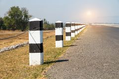 Milestones, black and white milestones with green grass roadside,. Lake roadside in background,concept for next step.go on Stock Photo