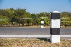 Milestones,black and white milestones with green grass roadside,. Lake roadside in background,concept for next step.go on Stock Photo