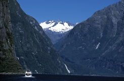 Milford Sound, New Zealand. Milford Sound, Fiordland NP, New Zealand with tour boat barely visable and snow capped mountains in background Royalty Free Stock Photos