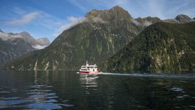 Milford Sound, New Zealand - May 2, 2015: Spirit of Milford boat cruising through the fiords in Milford Sound, South Island New Ze royalty free stock photos
