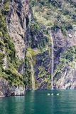 Kayakers enjoy the scenery and waterfalls of Milford Sound, one of New Zealand`s most popular tourist destinations royalty free stock images