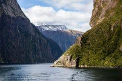 Milford Sound snö täckte Mountainin når en höjdpunkt i vatten arkivfoto